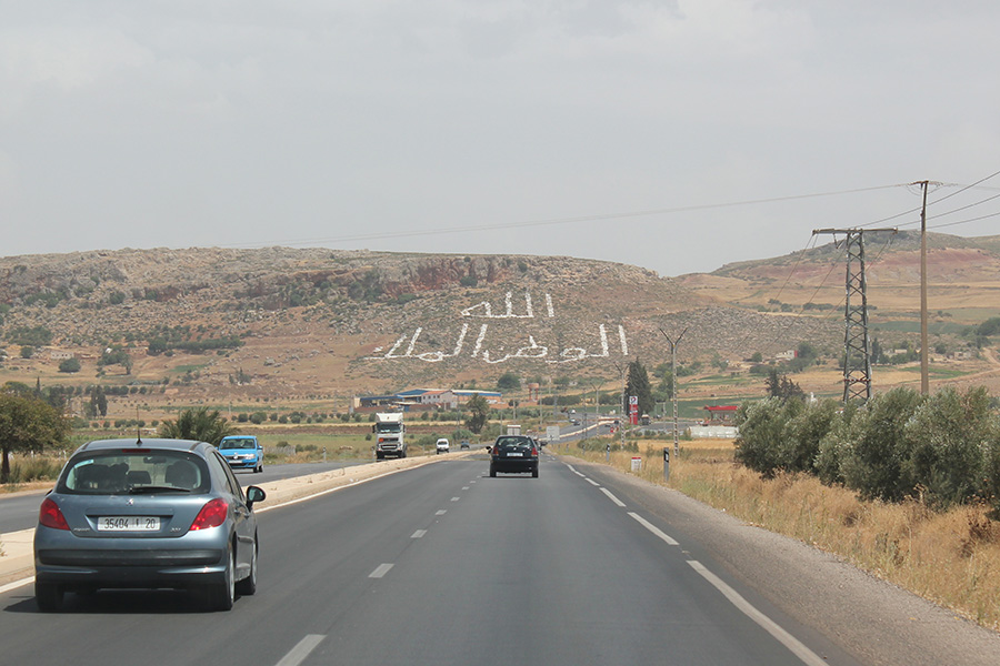 "Road leading from Meknes to Ifrane with Morocco's national motto (Allah ""God,"" Al-Watan ""Nation,"" and Al-Malik ""King"") painted on hillside at town of El Hajeb. Photo by Jonathan Wyrtzen (2011)"